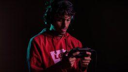 Chico con auriculares jugando en un smartphone