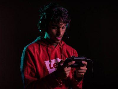 Imagen: Chico con auriculares jugando en un smartphone