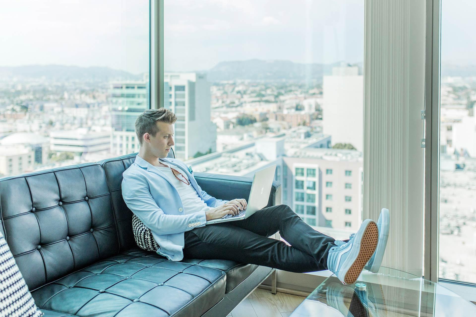 Hombre sentado en el sofá con un portátil